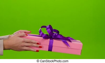 Gift of not small size shows in the hands of woman