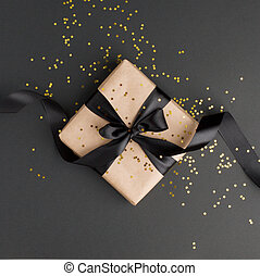 Gift or present box and gold stars confetti on black table top view. Flat lay composition for birthday, mother day, black friday sale, xmas, christmas, new yaer or wedding.