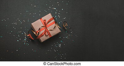 Gift or present box and stars confetti on dark table top view. Birthday or party greeting card with copy space, hen party invite