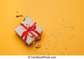 Gift or present box and stars confetti on yellow table top view. Flat lay composition for birthday, mother day or wedding.