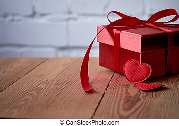 Gift or present box with red bow ribbon and glitter heart on rustic background for Valentines day.