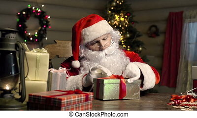 Gift Packing - Close up of Santa Claus packing gifts in...