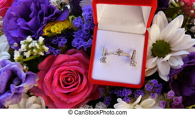 Gift present red box with a set of engagement ring and earrings on the background of a multi-colored beautiful bouquet of flowers. Marriage proposal. White gold or silver with diamond stone.