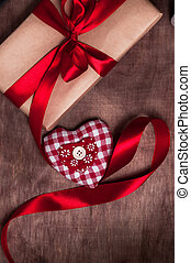 Gift tied with ribbon and red heart on wooden background. Valentine's day.