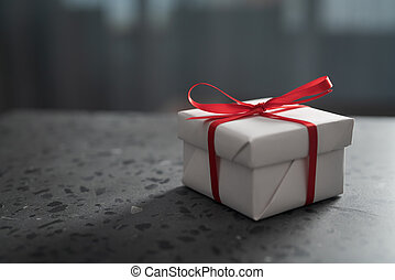 Gift white box with red bow on a gray concrete countertop