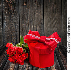Gift with a bouquet of roses on a wooden background