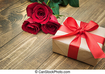 Gift with a red ribbon and a bouquet of roses on your...