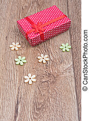 Gift with flowers on a wooden background