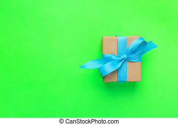 gift wrapped and decorated with blue bow on green background with copy space. Flat lay, top view