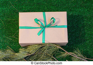 Gift wrapped in Kraft paper on a green background with branches of cedar.