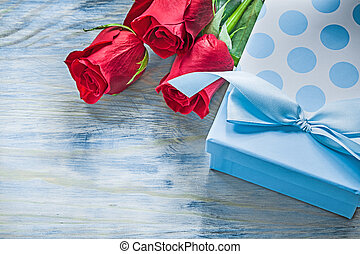 Giftbox scented red roses on wooden board celebrations concept