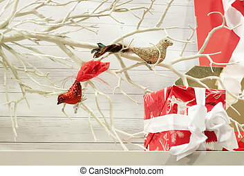 gifts by bird ornaments in bare tree