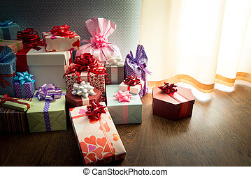 Colorful christmas gifts with ribbon on the floor, assorted colors and sizes.