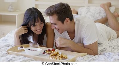 Giggling couple having breakfast in bed - Attractive young...