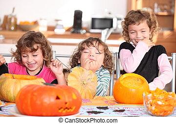 Giggling girls carving pumpkins