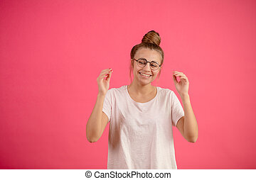 giggling short-sighted female teenager with raised hands