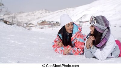 Giggling twins laying down at ski slope - Cute pair of...