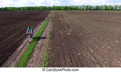 bycyclist riding bike in a field