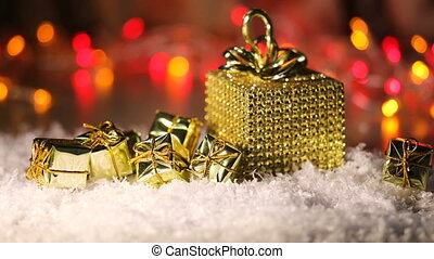 gilded boxes with gifts in the snow. Christmas background.
