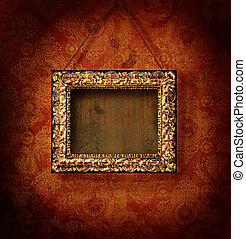 Gilded picture frame on antique wallpaper