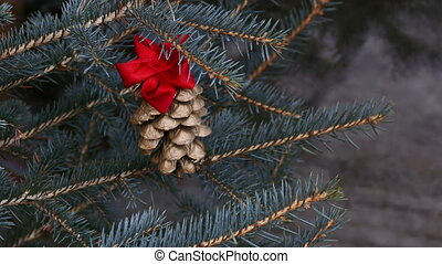Gilded pine cone in Christmas tree - Gilded pine cone with...
