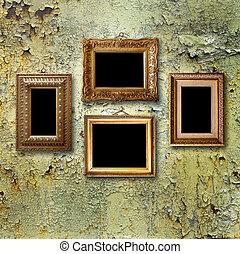 Gilded wooden frames for pictures on old rusty metallic wall...