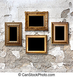 Gilded wooden frames for pictures on old stone wall