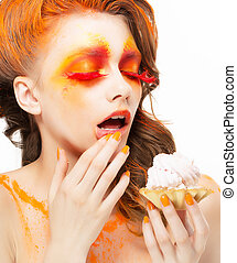 Gilding. Tempting Woman eating a Pie with Cream. Bright Red-Golden Makeup