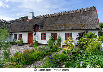 beautiful thatched roof house with a vegetable garden under a blue sky with white cumulus clouds