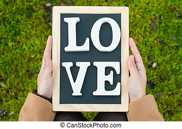 """gilr hands holding a blackboard with the words """" Love"""""""