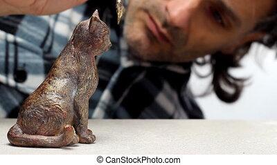 gilt-bronze statue - man doing gilding on a miniature