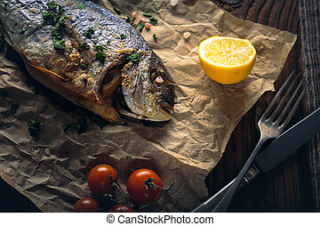 Gilthead seabream (Sparus aurata) baked in the oven. -...