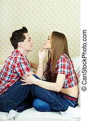 Amorous couple sitting on sofa, looking at one another and flirting