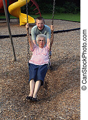 Teenage grandson pushing his grandmother on a playground swing.