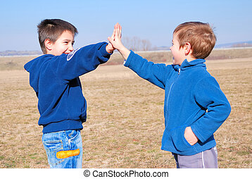 boys playing gimme five aoutside on a sunny day