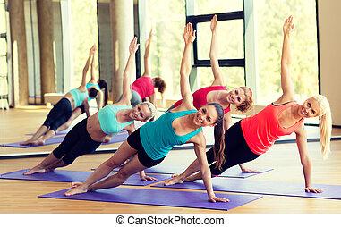 gimnasio, mujeres, meditar, estera, sonriente