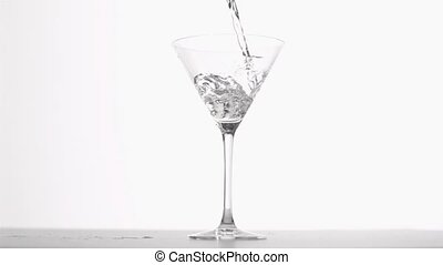 Gin poured in super slow motion in a glass against white...