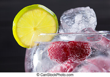 Gin tonic cocktail with raspberry and ice macro closeup -...