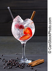 Gin tonic cocktail with strawberries cinnamon and juniper -...