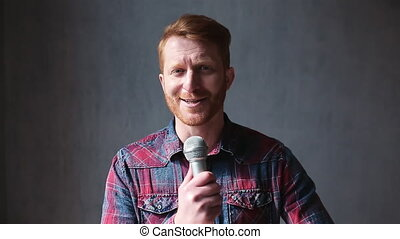 Ginger blogger guy making video at home with mic. Handsome young gentleman wearing jean shirt recording himself on video with microphone. Prores 422.
