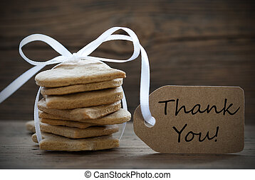 Ginger Bread Cookies with a white Bow and a Label on which stands Thank You, on wooden Background