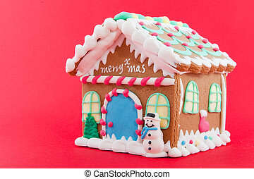 Ginger bread house isolated on red background