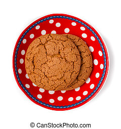 Some lovely ginger cookies on a colorful red and white dotted dish. Isolated on a white background.