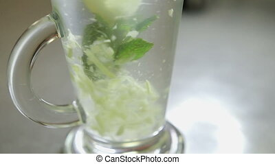 spoon stirring his tea with mint and lemon in a transparent glass, shot close-up