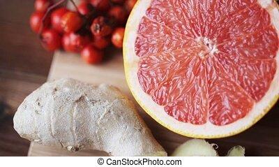 ginger, grapefruit, orange and garlic on board -...