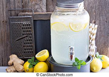 Ginger homemade lemonade in a beverage dispenser rustic...