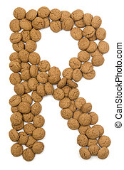 """Little ginger nuts in the form of the letter R. These little ginger nuts are used in Holland for the """"Sinterklaas"""" party, which is at Dec 5 every year. Sinterklaas is a sort of Santa Claus. In Holland these ginger nuts are called """"pepernoot"""". Isolated on white."""