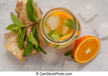 Ginger orange ice tea with mint in a glass jar, white background, copy space, top view. Summer refreshing drink concept.