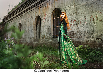 Ginger queen near the castle - Red-haired woman in a green ...