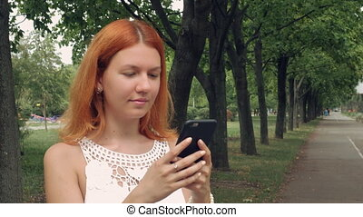 ginger student using smart phone outdoor.